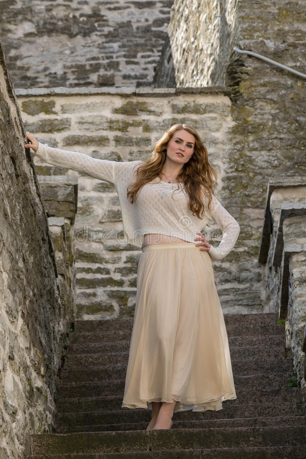 Kaukaski biały kobieta model i cegła kamień Piękna dziewczyna, długi czerwony włosy, beż spódnica i kardigan, Kobiety pozycja na  obrazy royalty free