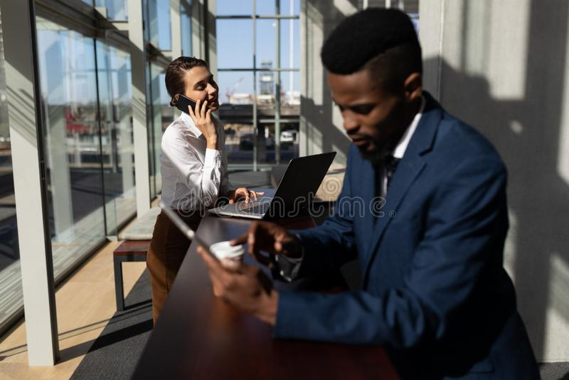 Kaukaski bizneswoman opowiada na telefonie komórkowym podczas gdy używać laptop w biurze obraz stock