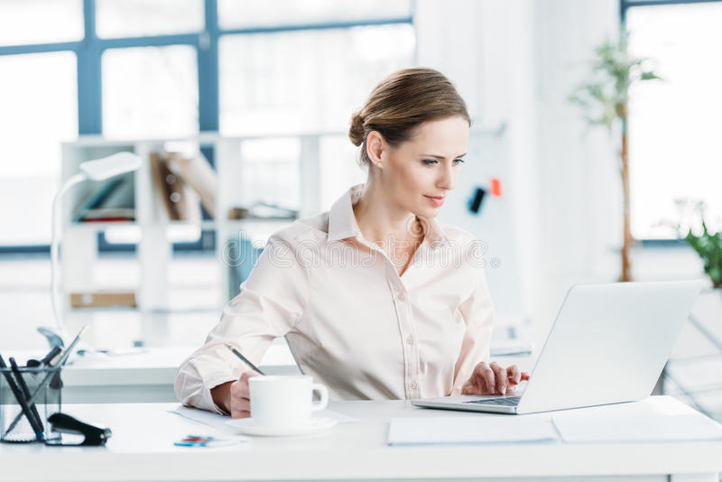 Kaukaski bizneswoman w formalwear pracuje na laptopie przy biurem zdjęcie royalty free