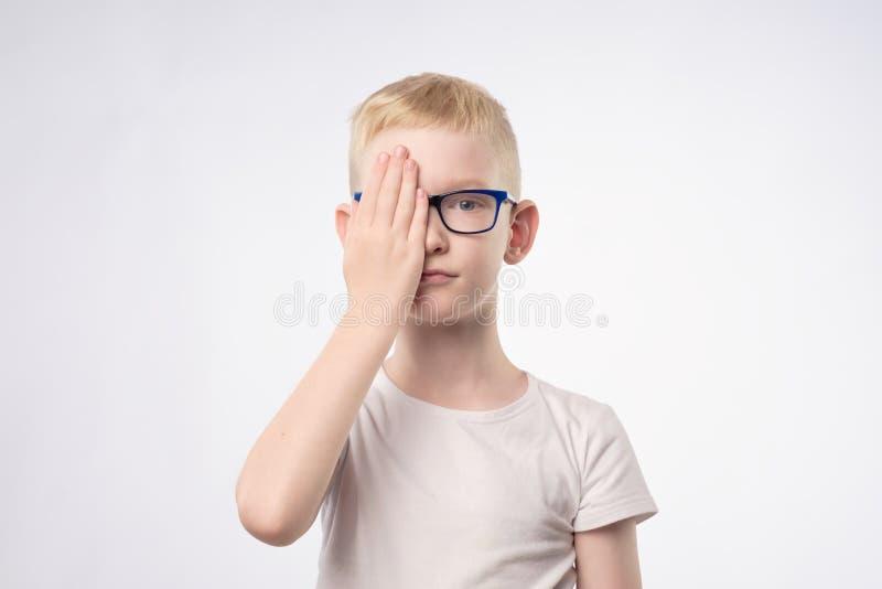 Kaukaski blond dziecko przegląda wzrok końcową połówkę twarz z ręką obrazy royalty free