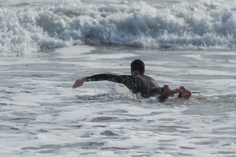 Kaukaski chłopiec z czarnym neoprenem przygotowanym do surfowania fotografia royalty free