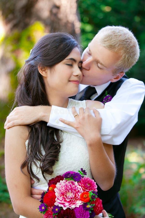 Kaukaski fornal czule całuje jego biracial panny młodej na policzku Di obraz stock