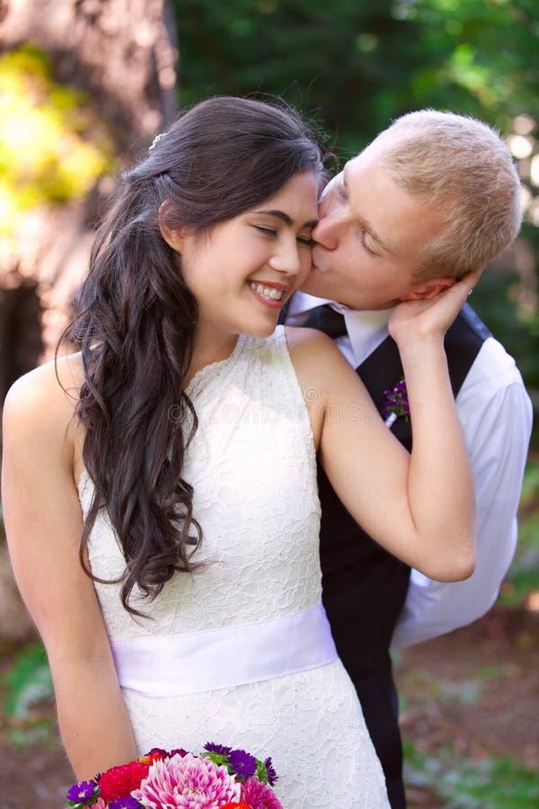 Kaukaski fornal czule całuje jego biracial panny młodej na policzku Di fotografia royalty free