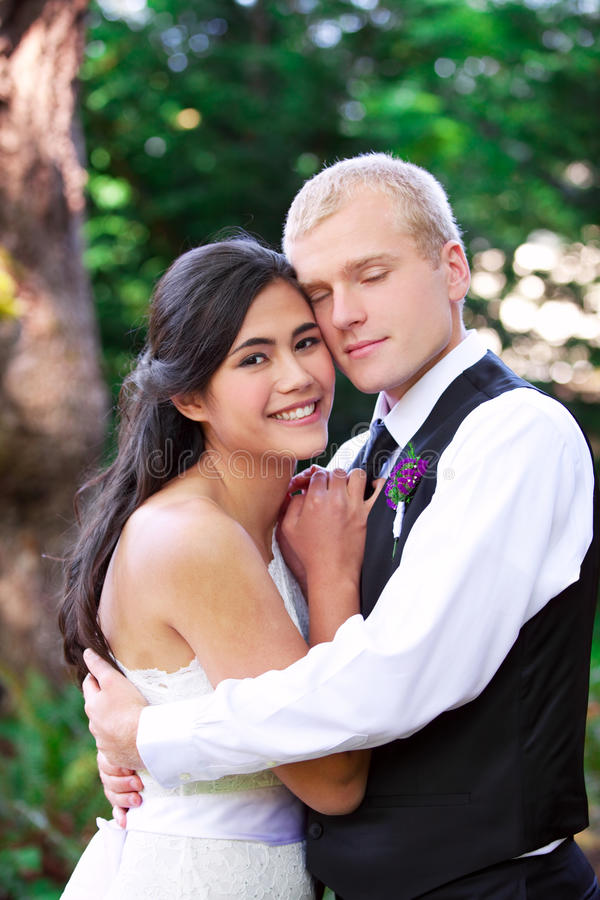 Kaukaski fornal trzyma jego biracial panny młodej, ono uśmiecha się Różnorodny cou zdjęcie stock