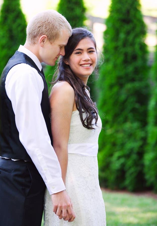 Kaukaski fornal trzyma jego biracial panny młodej, ono uśmiecha się Różnorodny cou zdjęcia stock