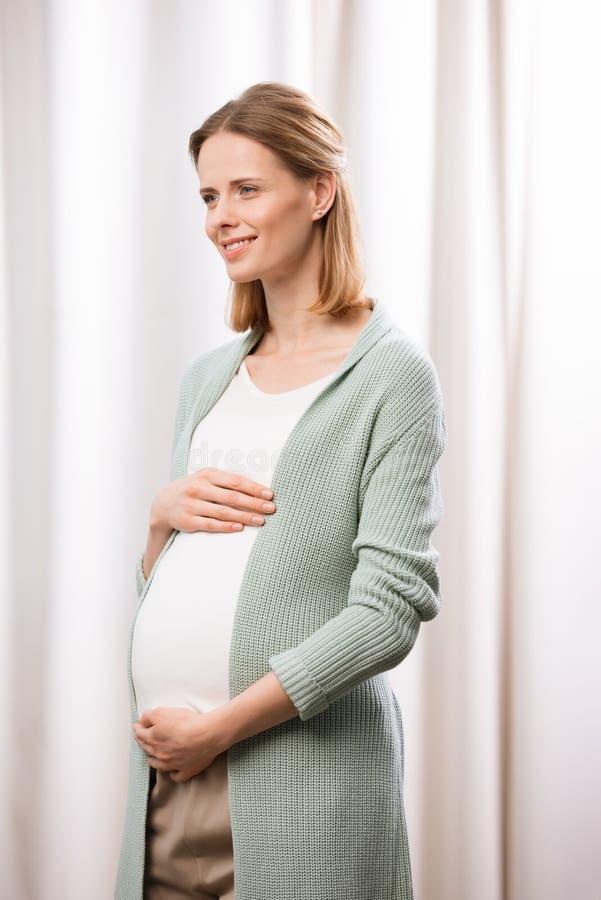 Kaukaski kobieta w ciąży uśmiecha się żołądek i trzyma zdjęcie stock