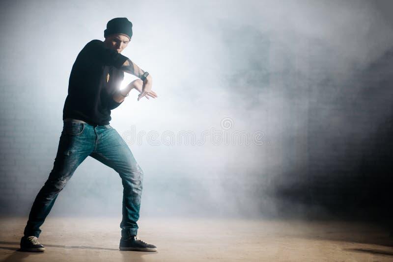 Kaukaski mężczyzna jest ubranym czarnej nakrętki dancingowego tecktonik na ulicie zdjęcie stock