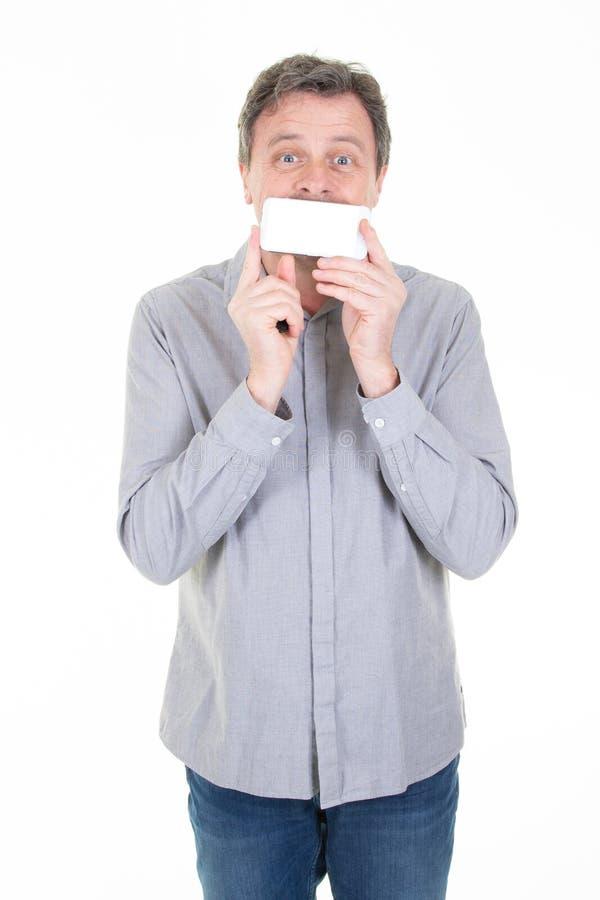 Kaukaski mężczyzna nad bielu ściennego seansu pustym ekranem smartphone pokrywy usta zdjęcia royalty free