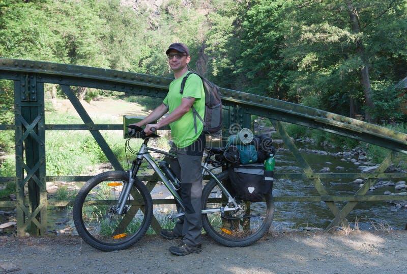 Kaukaski mężczyzna z jego mtb rowerem na moscie w lecie mo obrazy stock