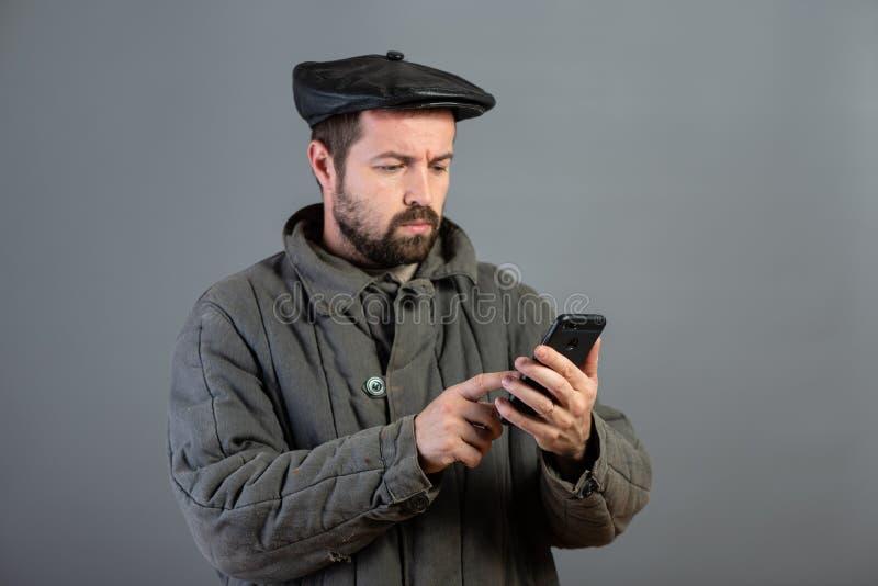 Kaukaski mężczyzny 35 lat z skoncentrowanym spojrzeniem przy smartphone, studio strzał Pomysł wioska mieszkaniec i nowożytna tech obraz royalty free