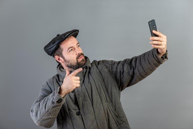 Kaukaski mężczyzny 35 lat z skoncentrowanym spojrzeniem przy smartphone, studio strzał Pomysł wioska mieszkaniec i nowożytna tech obrazy royalty free