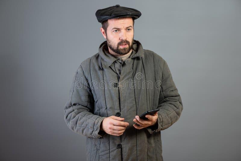 Kaukaski mężczyzny 35 lat z skoncentrowanym spojrzeniem przy smartphone, studio strzał Pomysł wioska mieszkaniec i nowożytna tech obrazy stock