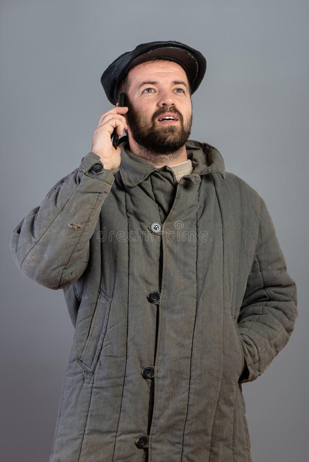 Kaukaski mężczyzny 35 lat z skoncentrowanym spojrzeniem przy smartphone, studio strzał Pomysł wioska mieszkaniec i nowożytna tech zdjęcia royalty free