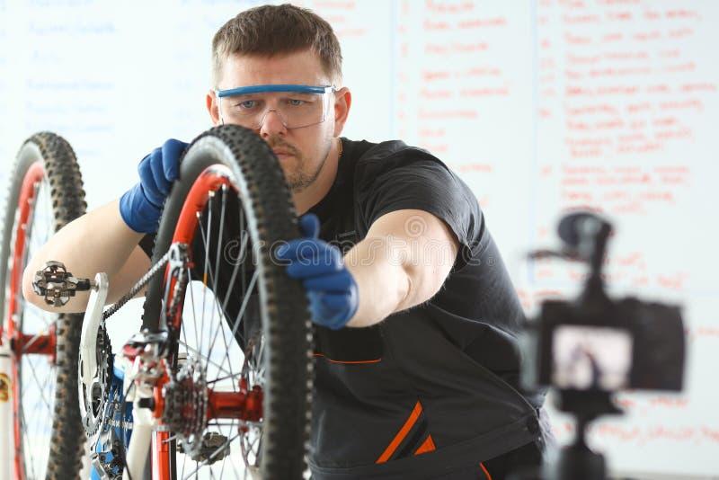 Kaukaski młodego człowieka naprawiania bicykl przy warsztatem fotografia royalty free