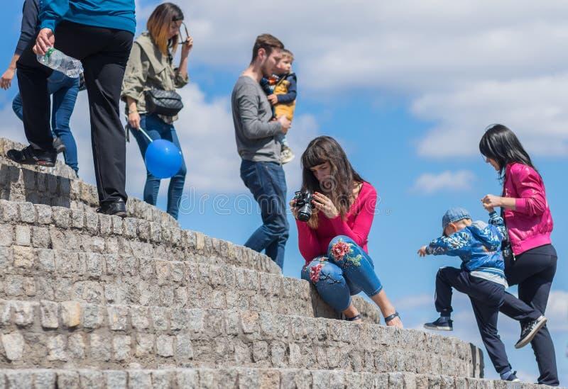 Kaukaski młodej kobiety obsiadanie na kamiennych krokach i dopatrywanie obrazkach od cyfrowej kamery ekranu zdjęcia royalty free
