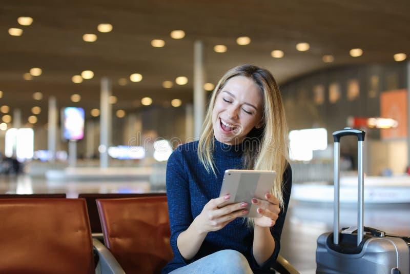 Kaukaski młodej kobiety obsiadanie w lotniskowej poczekalni z valise i używać pastylką obrazy stock