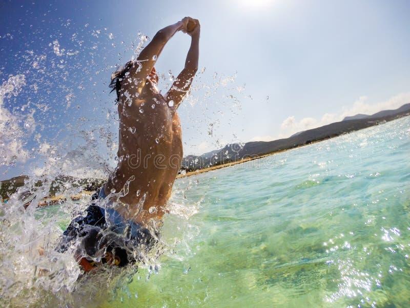Kaukaski młody chłopiec doskakiwanie w wodzie, bawić się zabawę i mieć obraz royalty free