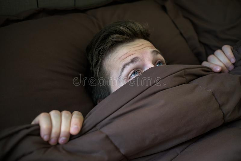 Kaukaski młody człowiek chuje w łóżku pod koc w domu obraz stock