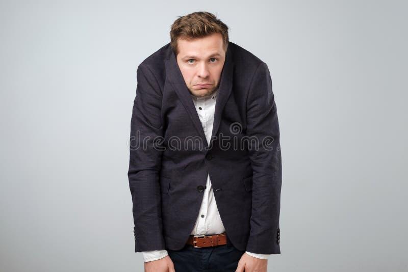 Kaukaski młody człowiek w zbyt dużym kostiumu Jest obrażający i patrzejący stresujący się zdjęcie royalty free