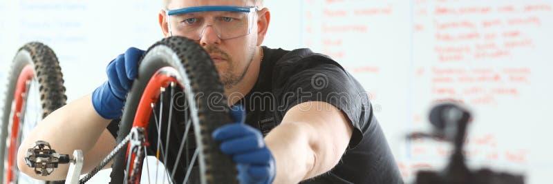 Kaukaski m?odego cz?owieka naprawiania bicykl przy warsztatem zdjęcie royalty free