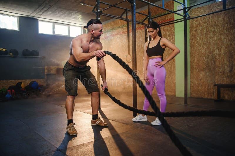 Kaukaski sporta mężczyzna robi batalistycznemu linowemu ćwiczeniu pod kontrolą trener w gym zdjęcia stock