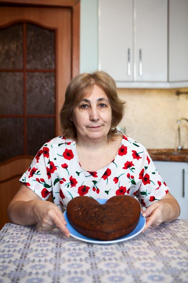 Kaukaski starszy kobiety mienia serce kształtował tort na talerzu podczas gdy siedzący w swój domowej kuchni zdjęcia stock