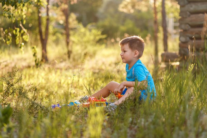 Kaukaski z włosami chłopiec obsiadanie w trawie w lecie obrazy royalty free