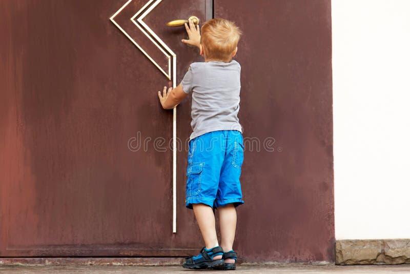 Kaukaskie chłopiec próby otwierać dużego drzwi obraz stock