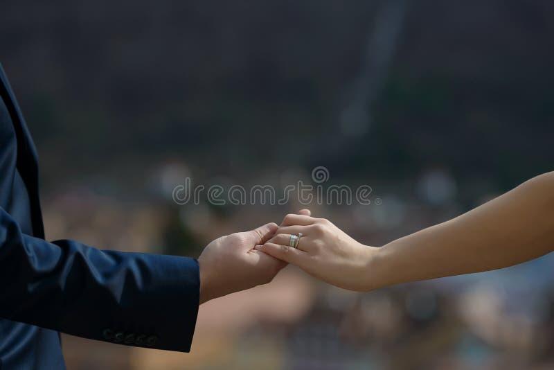 Kaukaskie pary mienia ręki z widocznym zobowiązaniem i obrączkami ślubnymi fotografia royalty free