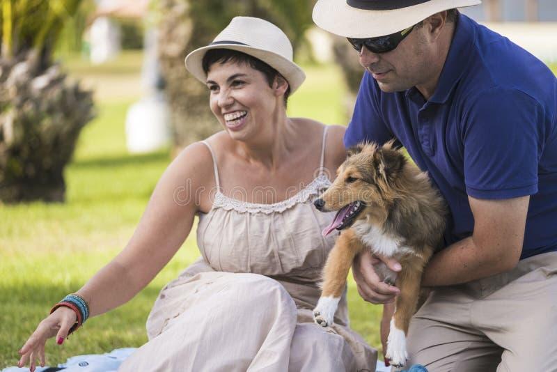 Kaukaskiego wieka średniego rozochocona para w plenerowej czas wolny aktywności bawić się z ładnym pięknym szczeniaka Shetland ps obraz royalty free