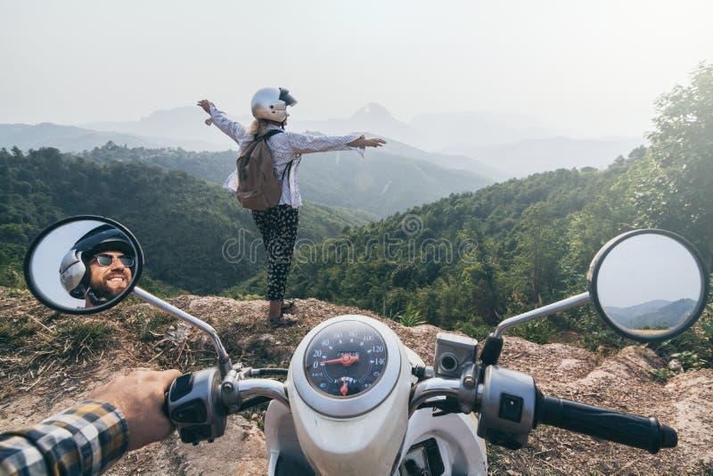 Kaukaskiej pary jeździecki motocykl w Laotian górach Kobieta stojaki na falezie ostrzą, ręki w górę Nong Khiaw wioska, Laos zdjęcie royalty free