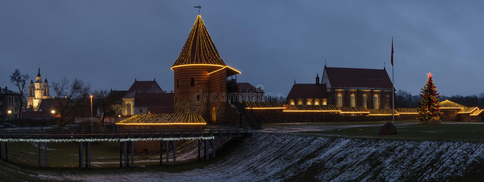 Kaunas castle in Christmas night view panorama. Panoramic view of Old castle and St. George church in Christmas time illuminated with lights, Kaunas, Lithuania royalty free stock photography