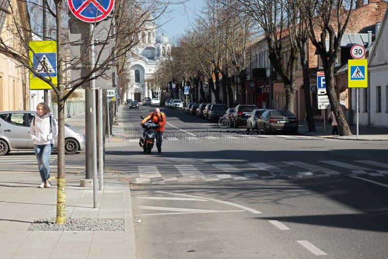 Kaunas, Lithuanie, le 15 avril 2019 : Un homme pousse son scooter au stationnement photo libre de droits