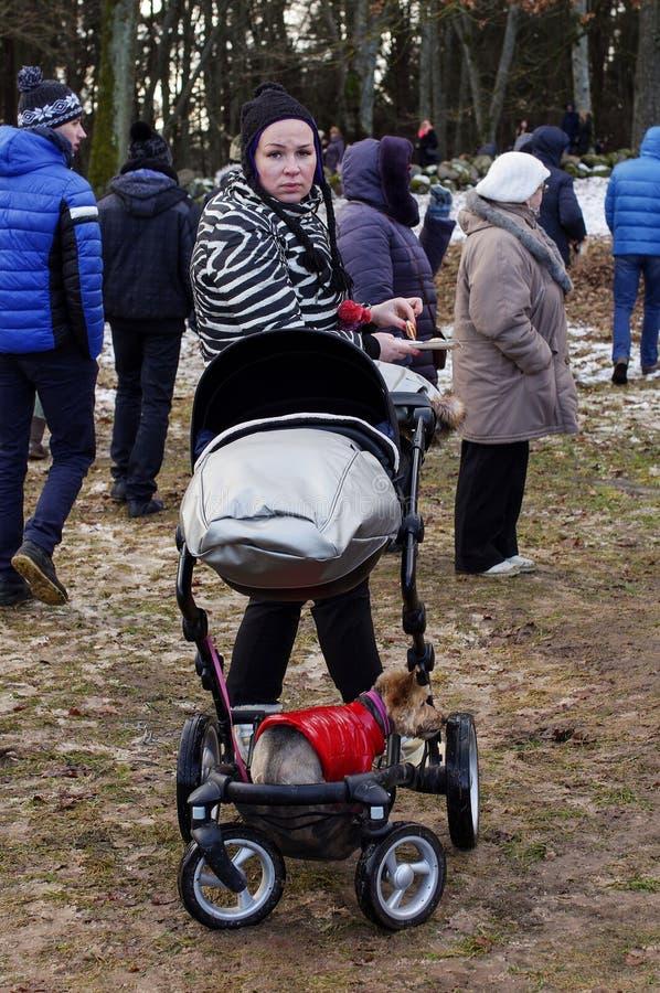 KAUNAS, LITUÂNIA - 25 DE FEVEREIRO: Senhora moderna nova com st da criança foto de stock