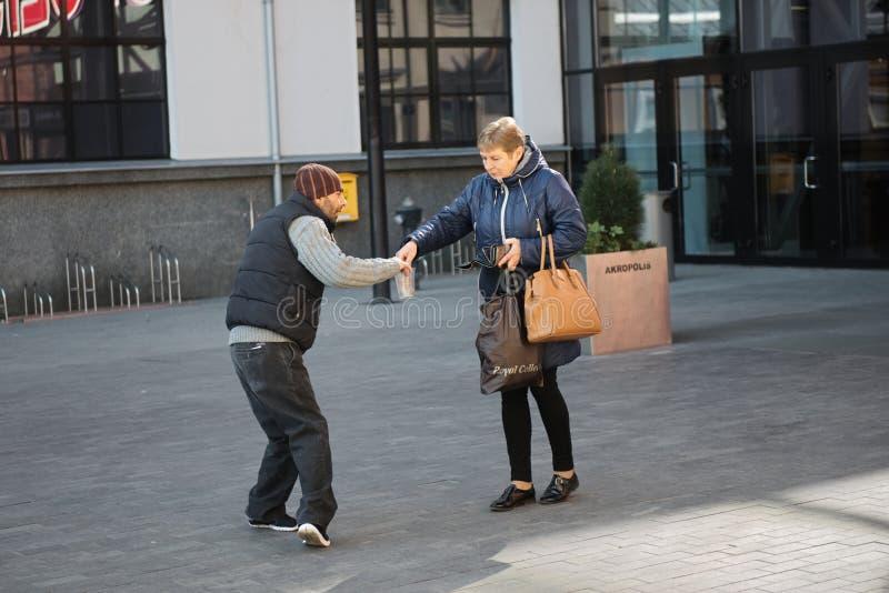 Kaunas, Lituania, il 15 aprile 2019: donna che dà alimento all'uomo senza tetto del mendicante fotografia stock