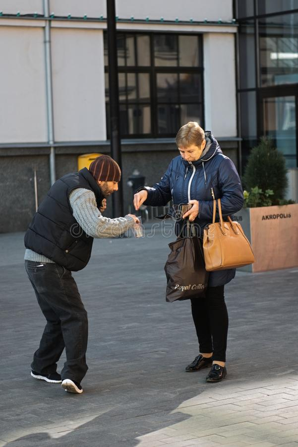 Kaunas, Lituania, il 15 aprile 2019: donna che dà alimento all'uomo senza tetto del mendicante immagini stock
