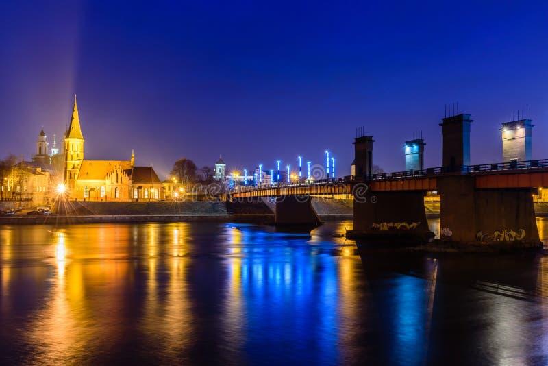 Kaunas at night. Illuminated bridge across Nemunas river and old town cityscape at night, Kaunas, Lithuania royalty free stock image