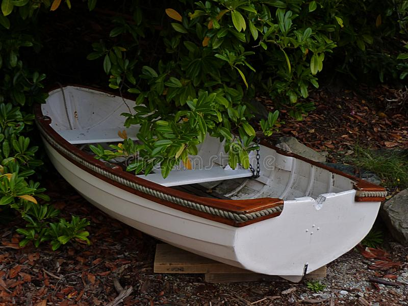 Kauri clinker dinghy underneath bushes. Wooden kauri clinker dinghy underneath bushes at the seaside royalty free stock photo