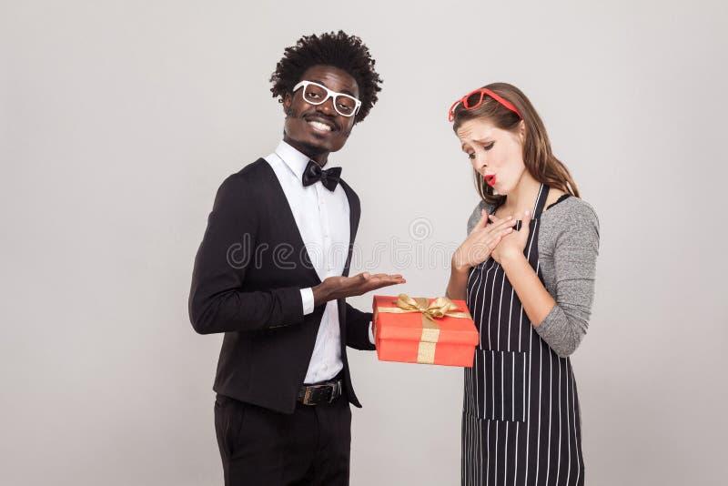 Kavalier gibt einem Geschenk für St.-Valentinsgruß ` s Tag ihren Freund stockbild