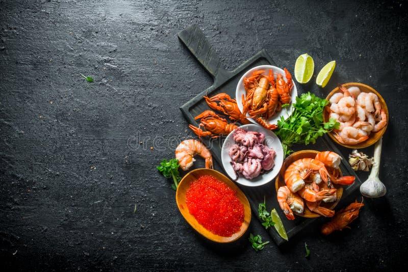Kaviaar en zeevruchten op een knipselraad met kruiden en kalkplakken stock fotografie