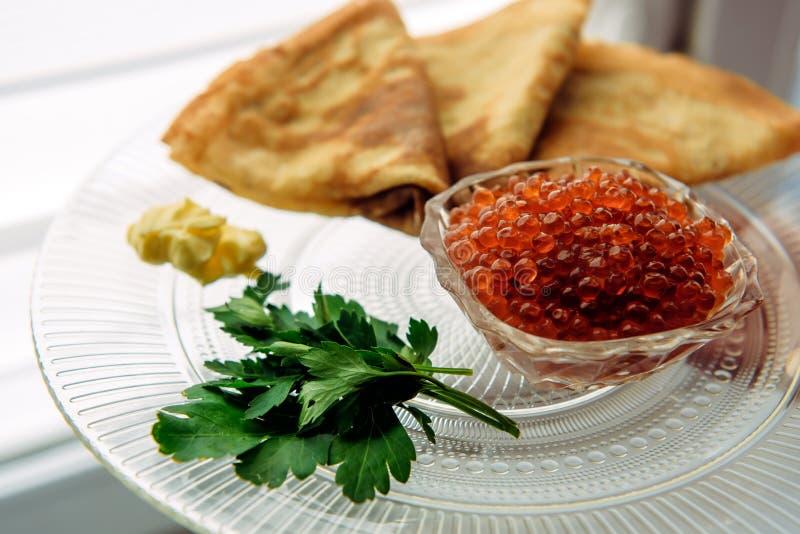 Kaviar för röd lax med pannkakor och persilja på en exponeringsglasplatta, selektiv fokus arkivbild