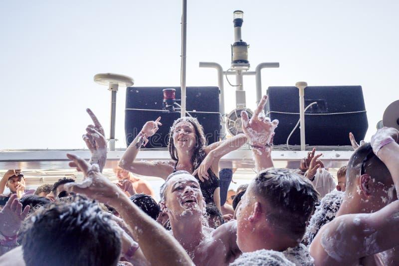 KAVOS, CORFU/GREECE- 22-ОЕ ИЮНЯ 2019: Молодые великобританские создатели праздника partying на одном из много, так называемый, кр стоковые изображения