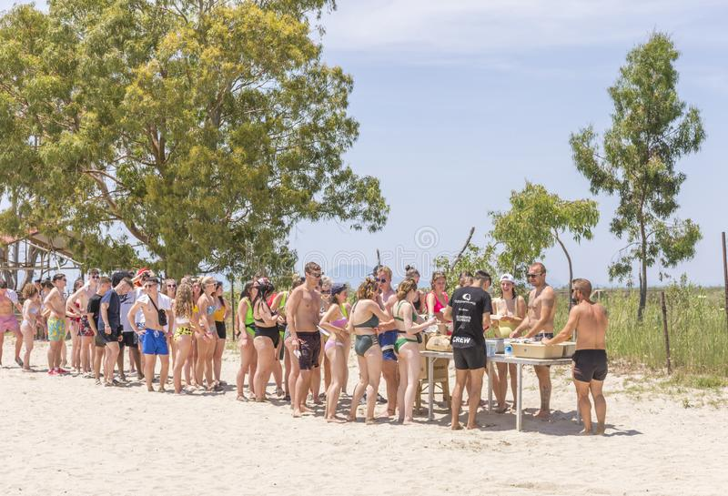 KAVOS,CORFU/GREECE-JUNE 22 2019:Young British holiday makers partying on one of the many ,so called ,booze cruise. BBQ break on the beach.Cruises stop in stock photo