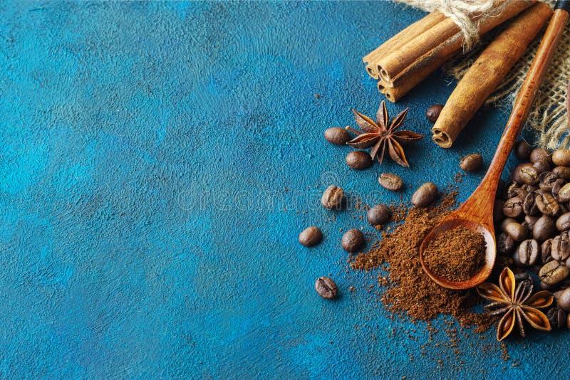 Kaw adra rozpraszać na błękitnym textural tle, anyżowych gwiazdach, cynamonowych kijach i zmielonej kawie w drewnianej łyżce, Odg fotografia royalty free