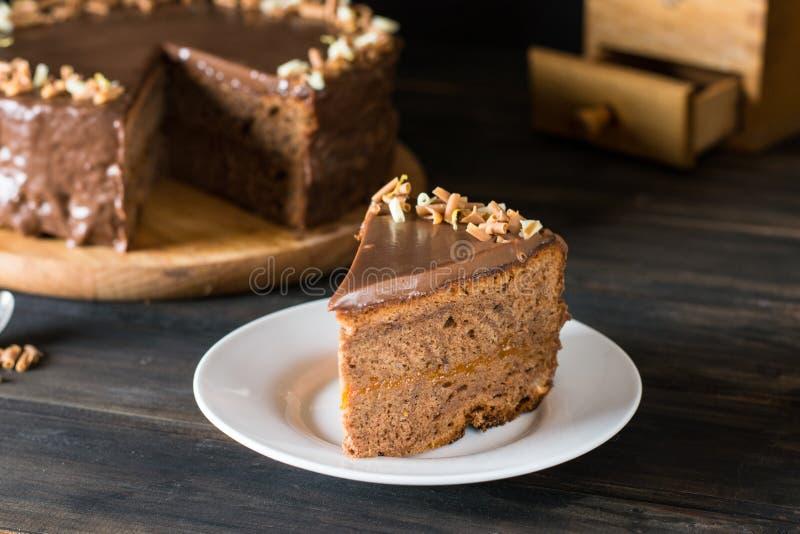Kawałek czekoladowy tort na białym talerzu na drewnianym Tradycyjny austriacki tort Sacher tort Morelowy kulebiak śniadaniowy kaw zdjęcia royalty free