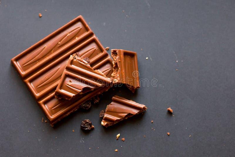 Kawały dojna czekolada z zdruzgotanymi hazelnuts i rodzynkami z alkoholem na czarnym tle Ciasteczka degustation zdjęcie royalty free