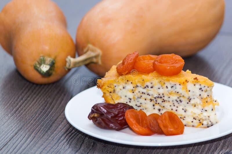 Kawałek dyniowy domowej roboty cheesecake z wysuszonymi morelami, maczek, pomarańcze, daktylowa owoc na drewnianym stole Dziękczy zdjęcie stock