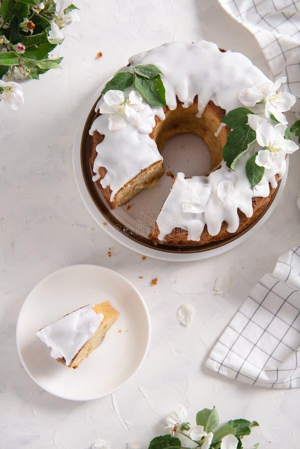 Kawałek jabłczany tort z cynamonem i lodowaceniem na białym tle z kwiatonośnymi jabłczanymi gałąź 9 trybowi stubarwni obrazki ust zdjęcie royalty free
