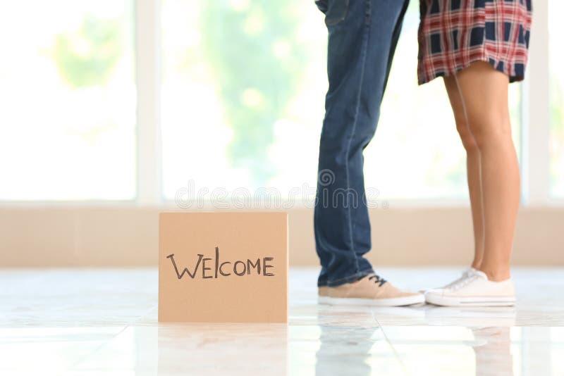 Kawałek karton z słowem powitanie i potomstwa dobiera się indoors fotografia stock