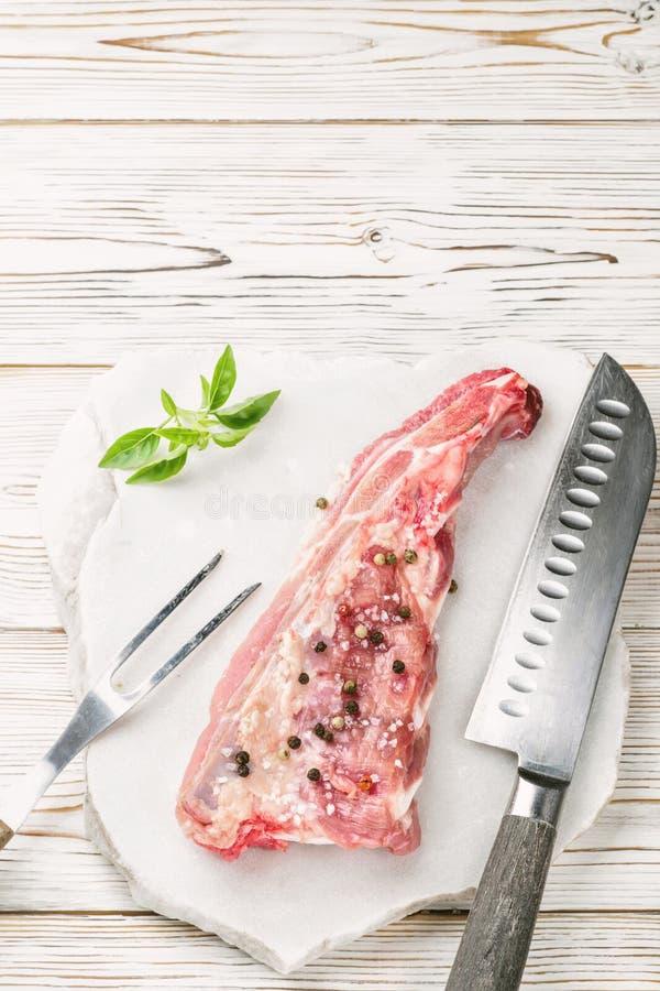 Kawałek mięso wieprzowiny brisket żebruje szpachelkę przyprawiającą z solą, pieprz i sprig basil zdjęcie royalty free